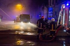 Los bomberos dirigen la corriente del agua en casa ardiente edificio en infierno llameante completo, y una lucha del bombero para Foto de archivo libre de regalías