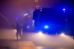 Los bomberos dirigen la corriente del agua en casa ardiente edificio en infierno llameante completo, y una lucha del bombero para Imagenes de archivo
