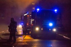 Los bomberos dirigen la corriente del agua en casa ardiente edificio en infierno llameante completo, y una lucha del bombero para Fotos de archivo libres de regalías