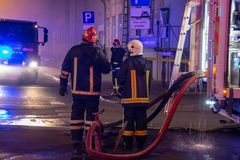 Los bomberos dirigen la corriente del agua en casa ardiente edificio en infierno llameante completo, y una lucha del bombero para Fotografía de archivo libre de regalías