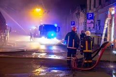 Los bomberos dirigen la corriente del agua en casa ardiente edificio en infierno llameante completo, y una lucha del bombero para Foto de archivo