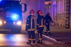 Los bomberos dirigen la corriente del agua en casa ardiente edificio en infierno llameante completo, y una lucha del bombero para Imagen de archivo libre de regalías