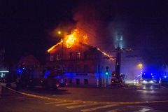 Los bomberos dirigen la corriente del agua en casa ardiente edificio en infierno llameante completo, y una lucha del bombero para Imágenes de archivo libres de regalías