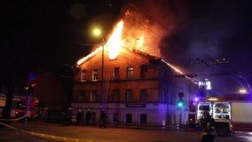 Los bomberos dirigen la corriente del agua en casa ardiente edificio en infierno llameante completo, y una lucha del bombero para almacen de video