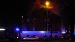 Los bomberos dirigen la corriente del agua en casa ardiente edificio en infierno llameante completo, y una lucha del bombero para almacen de metraje de vídeo