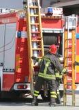 Los bomberos en la acción toman la escalera de madera Imagenes de archivo