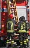 Los bomberos en la acción toman la escalera de madera Fotografía de archivo libre de regalías