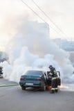 Los bomberos extinguen el coche quemado en la calle de la ciudad Imágenes de archivo libres de regalías