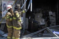 Los bomberos miran el daño hecho cuando un coche condujo en una tienda del suministro médico adentro fotos de archivo