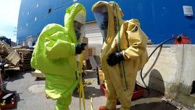 Los bomberos se preparan al escape de aislamiento de materiales tóxicos corrosivos peligrosos Imagen de archivo
