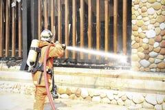 Los bomberos se preparan para atacar un fuego del propano durante un ejercicio de formación Foto de archivo