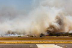 Los bomberos y el equipo luchan humo y las llamas negros Foto de archivo libre de regalías