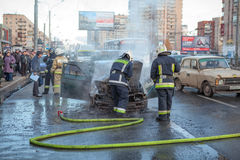 Los bomberos y el propietario están cerca de coche quemado en ciudad Imagenes de archivo