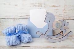 Los botines azules para el bebé, envuelven con la tarjeta vacía en un fondo de madera y un caballo de madera Fotografía de archivo
