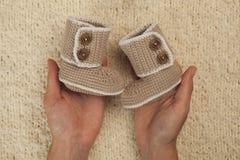 Los botines del bebé para el bebé recién nacido en manos de la madre, muchacha embarazada con la mano knetted los zapatos de bebé imagenes de archivo