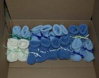 Los botines hechos punto del bebé del muchacho con las cintas se alinearon en fila - colores: Azul claro, azul marino, blanco fotografía de archivo libre de regalías