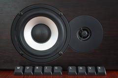 Los botones del teclado etiquetaron amor de la música delante del altavoz de madera fotos de archivo