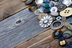 Los botones en grandes números dispersaron en los tableros de madera envejecidos Imagen de archivo