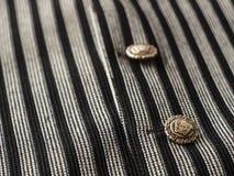 Los botones viejos en un ` s del hombre negro conceden el fondo con las rayas oscuras, cierre para arriba Foto de archivo libre de regalías