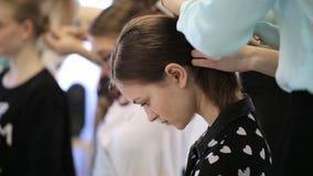 Los bowes hermosos de la muchacha su cabeza y esperan pacientemente hasta el final del procedimiento metrajes