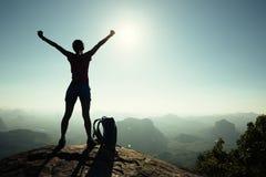 los brazos abiertos del caminante de la mujer en la montaña de la salida del sol rematan Imágenes de archivo libres de regalías