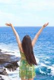 Los brazos adolescentes Biracial de la muchacha aumentaron por el agua del océano en alabanza Foto de archivo