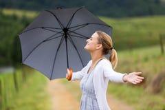 Los brazos de la mujer abren el paraguas Imágenes de archivo libres de regalías