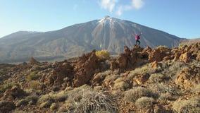 Los brazos de la mujer joven extendidos observan un cráter enorme del volcán de Teide, Tenerife, islas Canarias, España Abej?n a? almacen de video