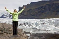 Los brazos del caminante de la mujer levantaron por Glacier In Icela Fotografía de archivo