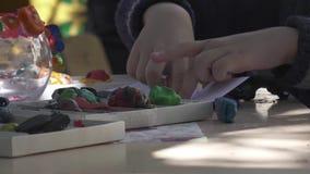 Los brazos del niño del muchacho esculpen figuras fuera del plasticine en la tabla en casa almacen de video