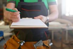 Los brazos del trabajador ofrecen el tablero con la pluma verde fotografía de archivo