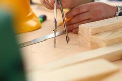 Los brazos del trabajador que hacen la estructura planean en el papel escalado imagen de archivo libre de regalías