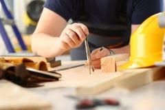 Los brazos del trabajador que hacen la estructura planean en el papel escalado fotografía de archivo