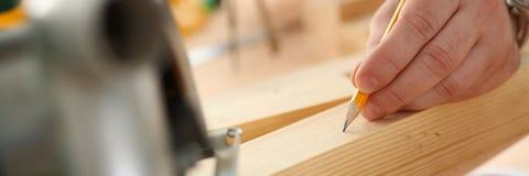Los brazos del trabajador que hacen la estructura planean en el papel escalado fotografía de archivo libre de regalías