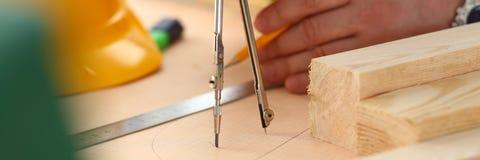 Los brazos del trabajador que hacen la estructura planean en el papel escalado fotos de archivo