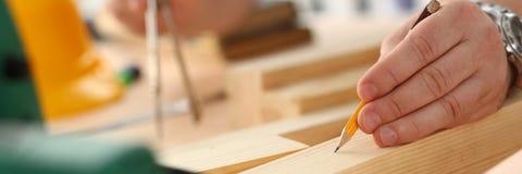Los brazos del trabajador que hacen la estructura planean en el papel escalado foto de archivo libre de regalías