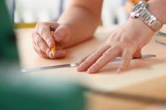 Los brazos del trabajador que hacen la estructura planean en el primer de papel escalado imagen de archivo