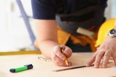Los brazos del trabajador que hacen la estructura planean en el primer de papel escalado imágenes de archivo libres de regalías