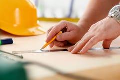 Los brazos del trabajador que hacen la estructura planean en el primer de papel escalado fotos de archivo