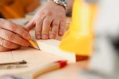 Los brazos del trabajador que hacen la estructura planean en el primer de papel escalado foto de archivo