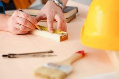 Los brazos del trabajador que hacen la estructura planean en el primer de papel escalado fotografía de archivo libre de regalías