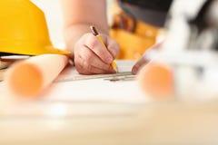 Los brazos del trabajador que hacen la estructura planean en el primer de papel escalado imagen de archivo libre de regalías