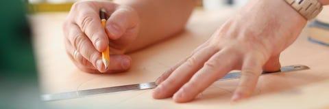 Los brazos del trabajador que hacen la estructura planean en el primer de papel escalado fotos de archivo libres de regalías