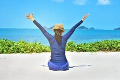 Los brazos felices de la mujer abren la libertad de la sensación que se sienta en la arena blanca Fotografía de archivo libre de regalías