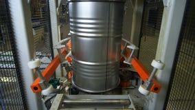 Los brazos mecánicos rojos transportan el barril del metal a lo largo de la cadena de producción almacen de video