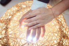 Los brazos se juntan con los anillos encendidos por la luz brillante Imagen de archivo
