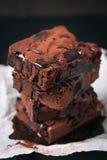 Los brownie dulces del chocolate hecho en casa se apelmazan con la cereza y salsa o jarabe de chocolate en un fondo oscuro, horiz Imagen de archivo libre de regalías