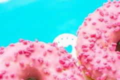 Los buñuelos esmaltados del rosa con el azúcar asperjan en el soporte con los corazones, fondo azul claro, copyspace, cumpleaños, Imagenes de archivo