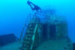 Los buceadores que exploran la nave arruinan en el mar tropical Imagen de archivo
