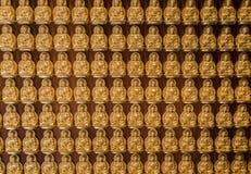 Los buddhas de oro se alinearon a lo largo de la pared del templo chino Foto de archivo libre de regalías
